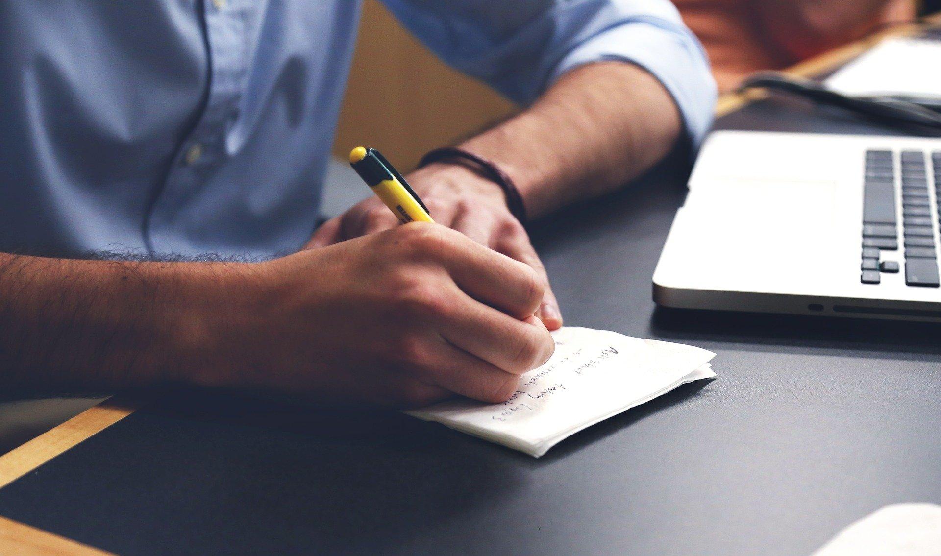 Schreibender Mensch neben Laptop
